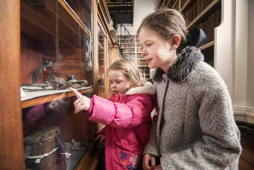 Children looking at the Beresford archeological collection
